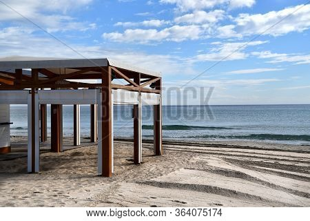 Empty Outdoor Terrace Cafe On Sand Beach. No People On Spanish Resorts During Coronavirus Quarantine