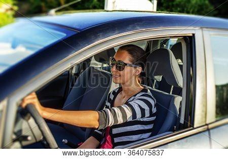 Girl Drives A Car On A Sunny Day.
