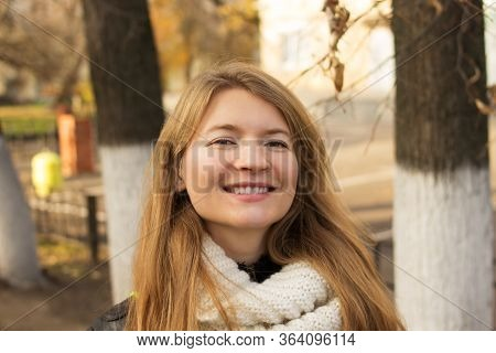 Smiling Cute Fair-haired Girl In The Autumn On The Street In A White Knitted Scarf, Against A Backgr