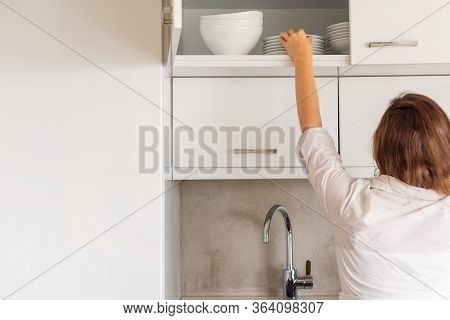 Back View Of Woman Putting Or Taking Clean Plate On The Shelf In Kitchen Cupboard. Housework Concept
