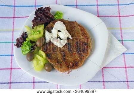 Balkan Cuisine. Pljeskavica - Grilled Dish Of Minced Meat - With Green Olives And Leaves Of Lettuce
