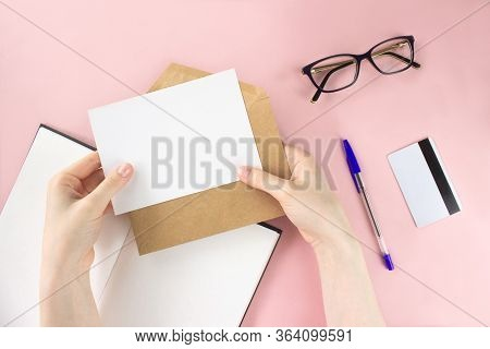 Female Hands Holding Envelope, White Card Mock-up With Copy Space On Pink Background. Notebook, Eyeg