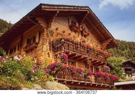 A Beautiful Wooden House Decorated With Flowers On The Balconies In The Swiss Alpine Village Griment