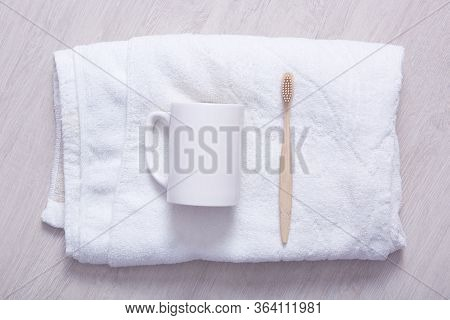 Styled Bathroom Counter With Soft Towel, Cup And Toothbrush. White Towel On Light Background, White