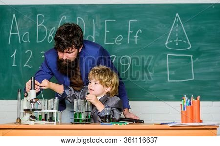 Childhood Upbringing And Education. Boy Pupil Achieving Education. Teacher And Child School Classroo