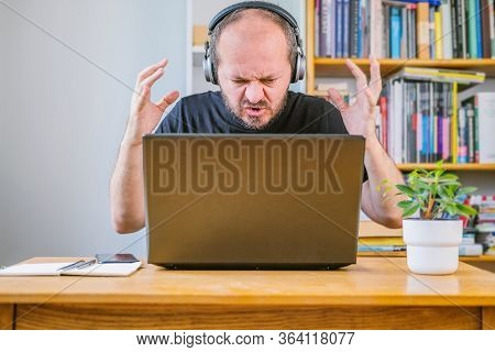 Man Working From Home Office, Angry Face Expression. Adult Bearded Man With Headphones Sitting Behin
