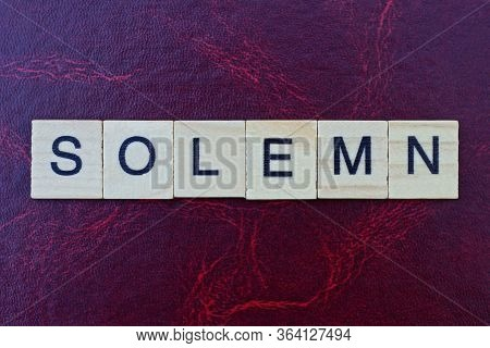 Word Solemn From Gray Wooden Small Letters With Black Font On An Red Background