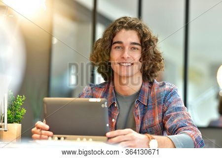 Portrait of smiling student working from home on tablet