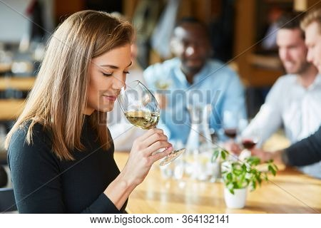 Young woman smells a glass of white wine during a wine tasting or tasting