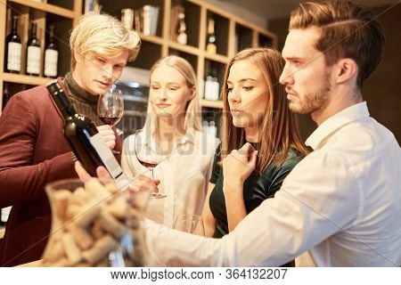 Friends in the wine shop during a wine tasting or tasting with a bottle of red wine