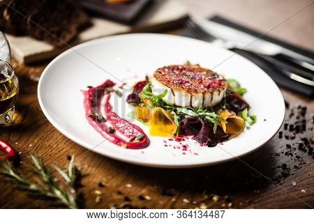 Grilled goat cheese salad Pickled beetroot pumkin, cranberry jam, pumkin seeds Delicious healthy mediterranean traditional vegeterian food closeup served for lunch in modern cuisine gourmet restaurant