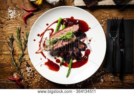 Duck breast with asparagus, purple carrot, demi-glace amd cherry sauce. Delicious healthy grilled and roasted bird fillet food closeup served on a table for lunch in modern cuisine gourmet restaurant.