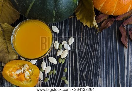 Pumpkin Juice In A Clear Glass Of Pumpkin And Dry Leaves On A Dark Background Top View