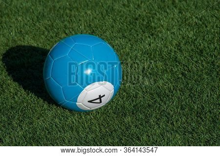 Blue Number 4 Soccer Billiards Or Pool Ball On Green Grass With A Shadow And Copy Space. Concept Of