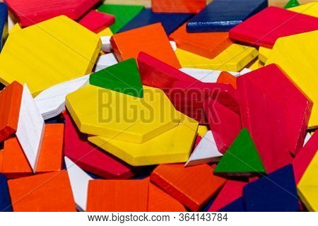 Bright Colored Tangram Child Geometric Shape Puzzle Pieces  In A Pile Close Up.