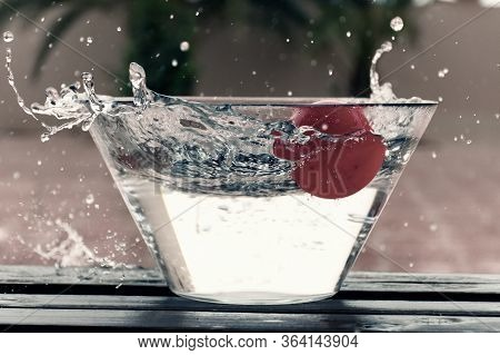 Red Ball Splashing In A Clear Bowl Of Water Creating Patterns And Texture Outdoors.