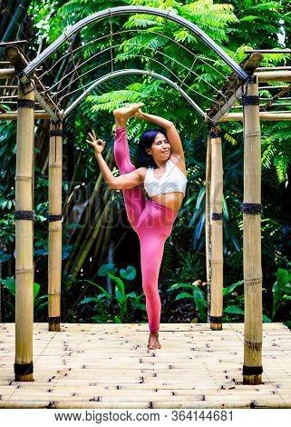 Yoga Practice Outdoor. Asian Yoga Teacher Practicing Utthita Hasta Padangusthasana, Extended Hand To