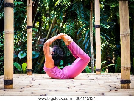 Yoga Practice Outdoor. Asian Yoga Teacher Practicing Dhanurasana, Bow Pose. Backbending Asana In Hat