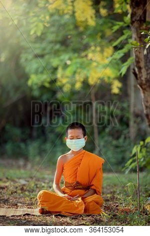 Novice Wearing Mask Meditation Under A Tree In The Temple With Lifestyle New Normal