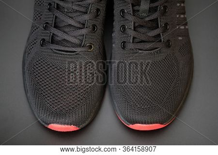 Black Sneakers With A Mesh And Black Laces Close Up. Mens Black Sneakers With A Red Sole On A Gray B