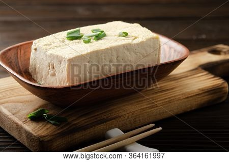 Soybean Tofu Vegetable Bean Curd In Clay Bowl On Kitchen Table With Chives And Chopsticks Aside