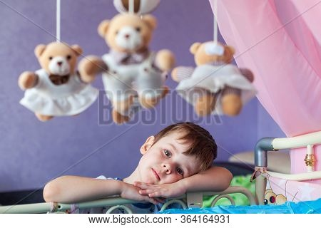 Adorable Little Boy Standing Near Cot With Baby Music Mobile Carousel. Big Brother Watches Younger S