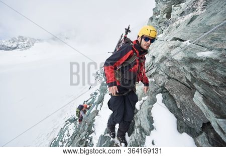 Full Length Of Male Mountaineer In Sunglasses Using Fixed Rope To Climb Winter Mountain. Alpinist In