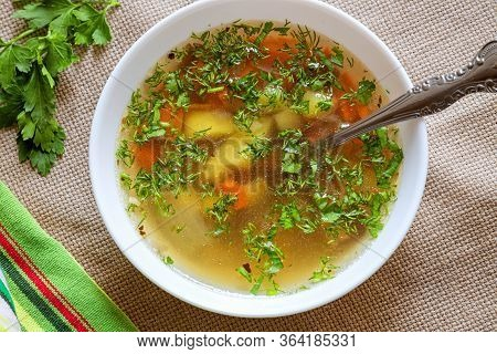 Vegetable Soup, Homemade Lunch Background, Broth With Vegetables And Herbs In A White Plate