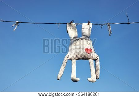 Forgotten Old Faded Toy Of Bunny Hanging On A Clothesline On Background Blue Sky.