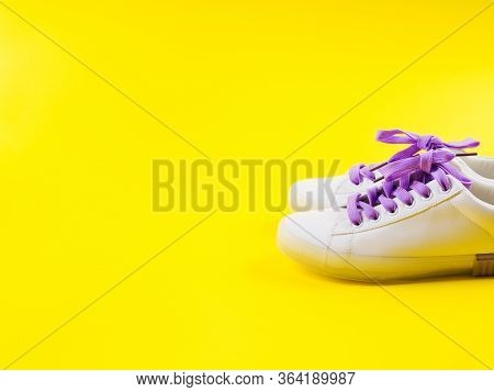 White Sneakers With Purple Laces On Yellow Background. Modern Minimal Fashion Art Trendy Bold Color