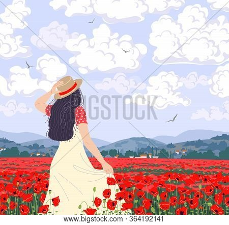 Young Woman Enjoys The Scenery Of Poppies Field. Dreamy Girl In Straw Hat Walking Among Red Poppy Fl