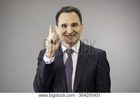 Handsome 40s Businessman Smiling Pointing Up With His Forefinger Isolated On Gray Background Copy Sp