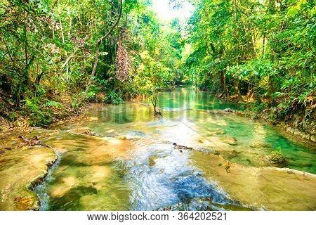 Tropical Rainforest Landscape With Flowing Stream And Sunrays. Erawan National Park, Kanchanaburi, T