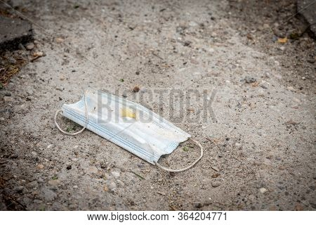 Used Face Mask, Disposable, Thrown Out On The Ground In The Environment As Garbage During The Corova