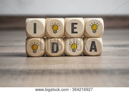 Cubes And Dice With Light Bulb Icon And Idea - Plan Do Check Act On Wooden Background