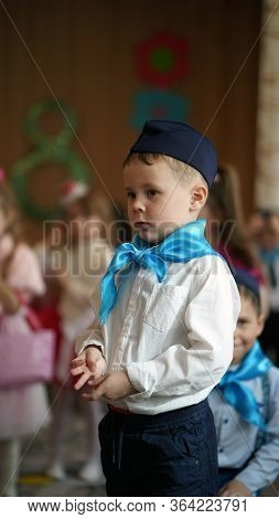 Portrait Of Cute Funny Boys In White Shirt And Blue Neckerchief In Kindergarten