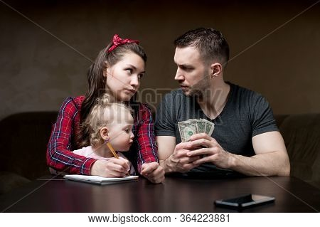 Counting Family Money. Husband And Wife Look At Each Other Seriously, A Little Daughter Sits On His