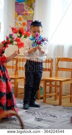 Portrait Of Cute Boys In White Shirt And Blue Neckerchief With Flowers In Kindergarten