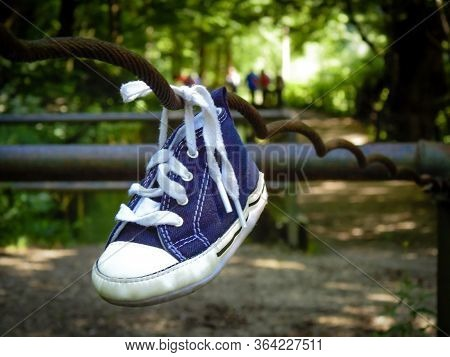 Forgotten Children Shoe Tied To A Fence