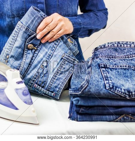 A Womans Hand Holds A Stack Of Clean Folded Ironed Things Made Of Blue Cotton Denim On The Ironing B