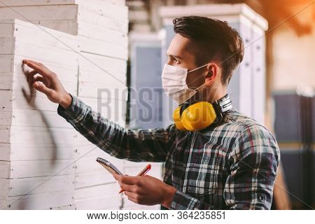 Portrait Male Foreman Inspector In Medical Face Mask And Protective Headphones Checking Woodwork Sto