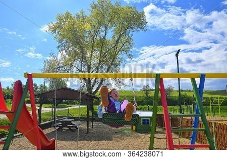 Happy Little Girl Playing Swing Outdoor In The Park. Happy Smiling Girl Child Sitting In Chain Swing