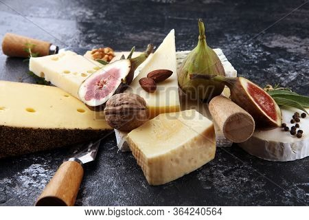 Cheese Plate Served With Figs, Various Cheese On A Platter On Rustic Table