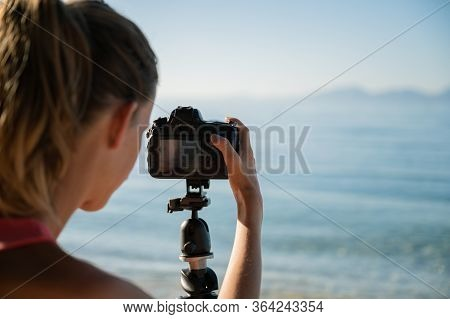Over The Shoulder View Of Female Photographer Arranging Camera Settings As She Is Getting Ready To S