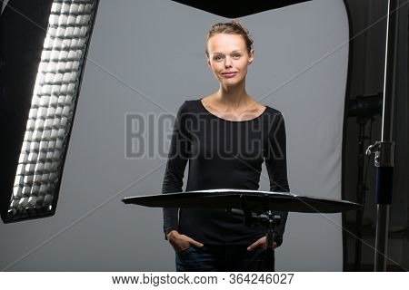 Beautiful female model posing in a photographic studio surrounded by professional strobe lights