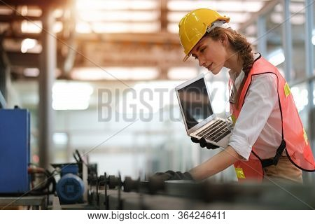 Pretty Engineer Or Technician Woman With Worker Uniform Hold Laptop Computer And Check Status Or Mai
