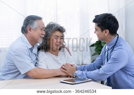 The Doctor With Blue Shirt And Stethoscope Encourage Old Man By Holding Their Hands And Woman About