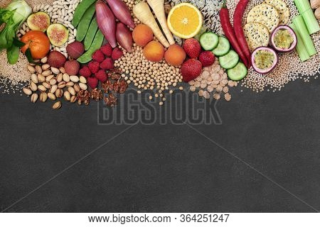Vegan health food background border with a large selection of foods. High in protein, vitamins, minerals, antioxidants, anthocyanins, fibre, omega 3 and smart carbs. Ethical food concept. Flat lay.