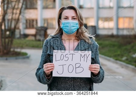 Woman In Mask Holds Sign Lost My Job. Concept Of Job Loss Due To Covid-19 Virus Pandemic. Female Sta