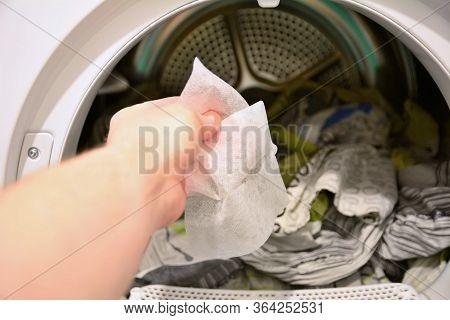 Hand Holding And Put Dryer Sheet Into A Tumble Clothes Dryer.